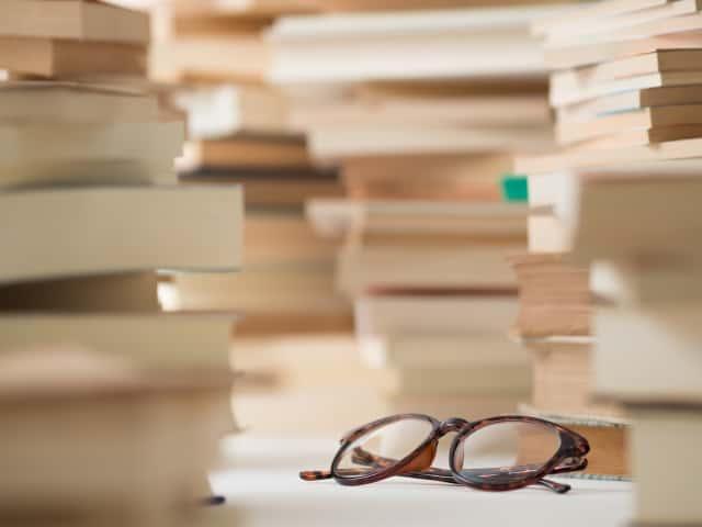 積まれた本とメガネ