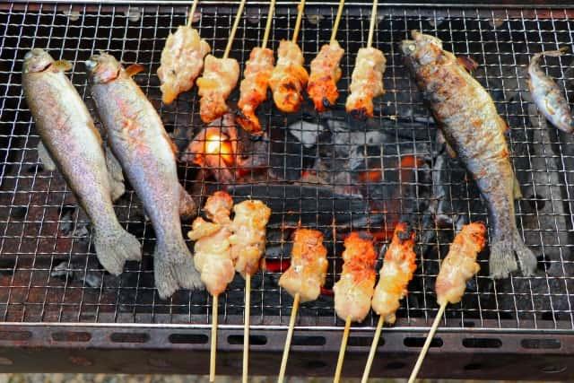 炭火、焼き鳥と魚が一緒の網の上にいる画像