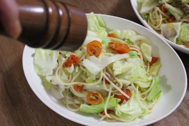 キャベツとトマトのパスタにミルで胡椒をかける